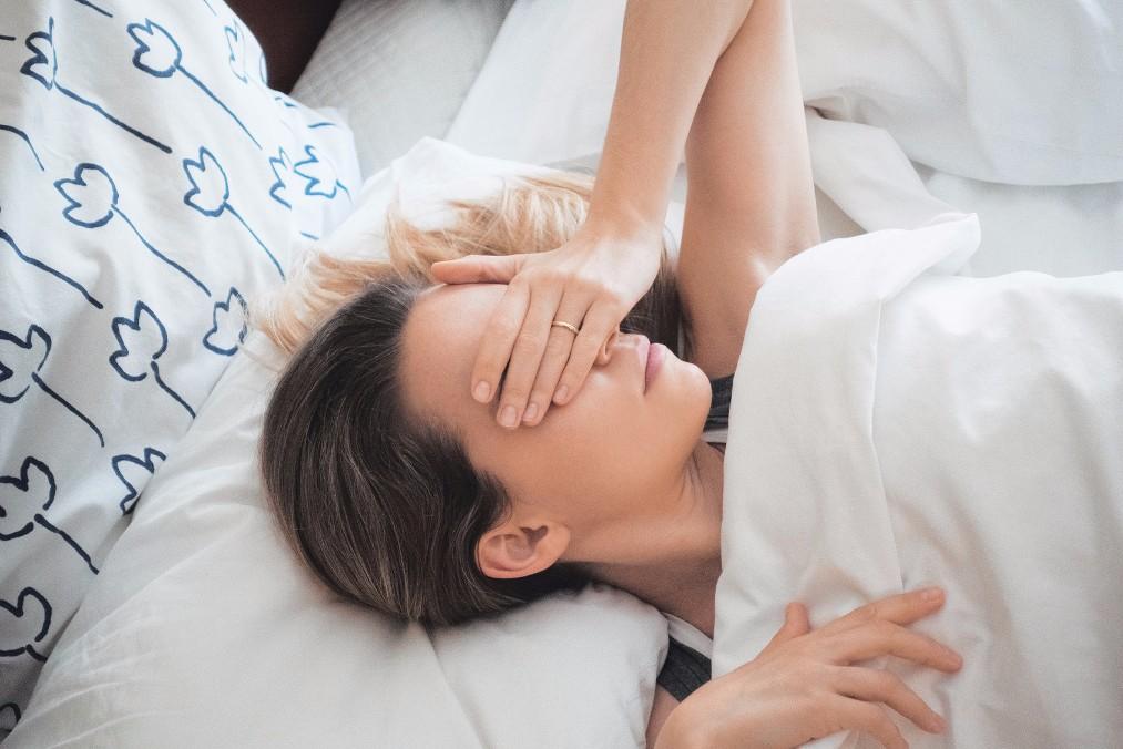 Един от признаците на пролетната умора е сънливостта - жена лежи в легло.