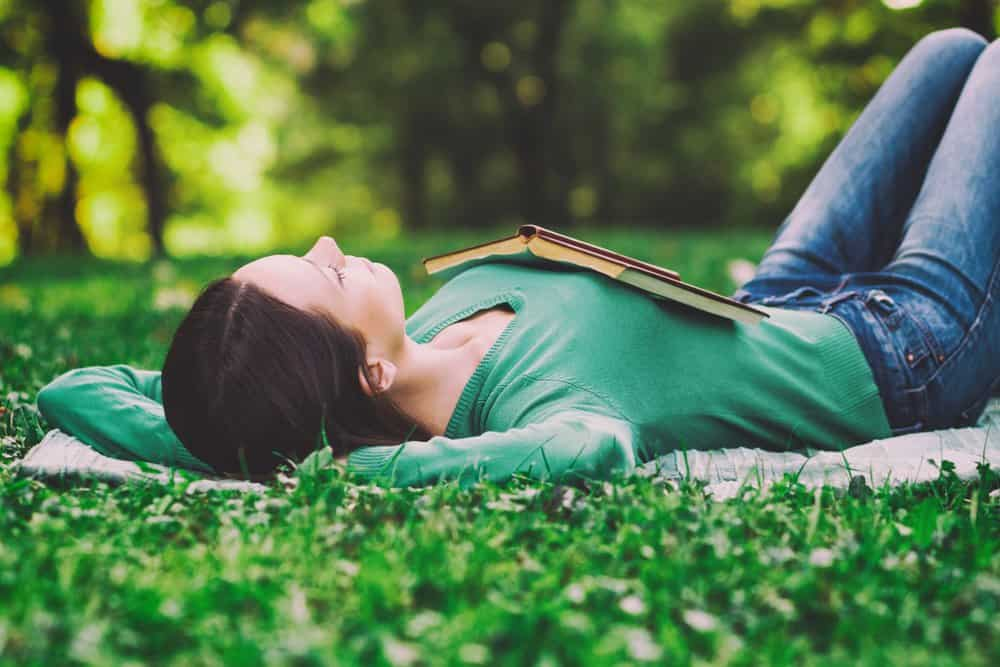 Жена почива, като е легнала върху трева.