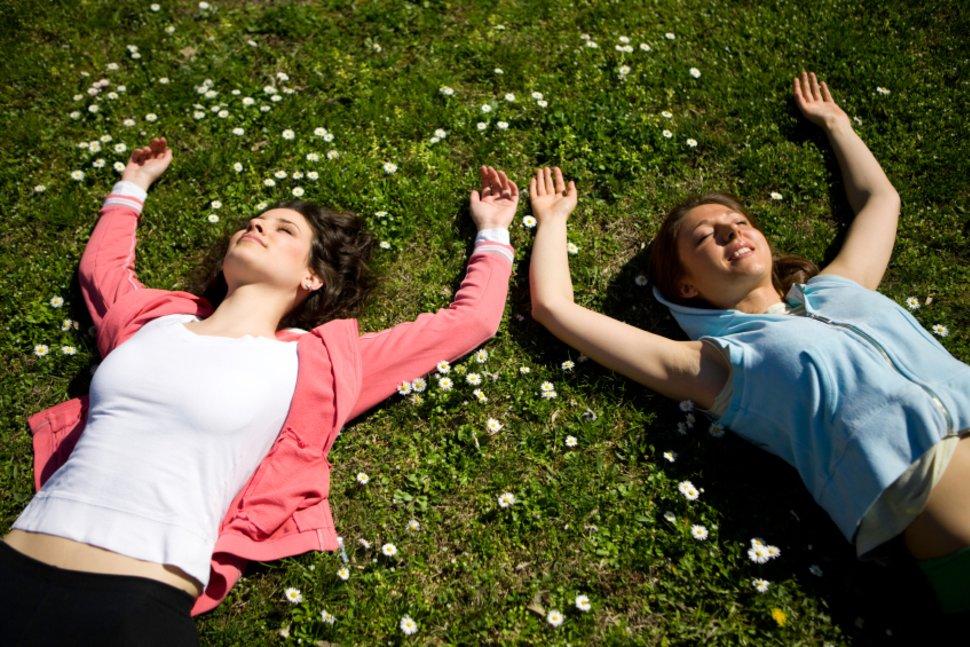 Пролетната умора те кара да се чувстваш отпаднал. На снимката, две момичета лежат на тревата.