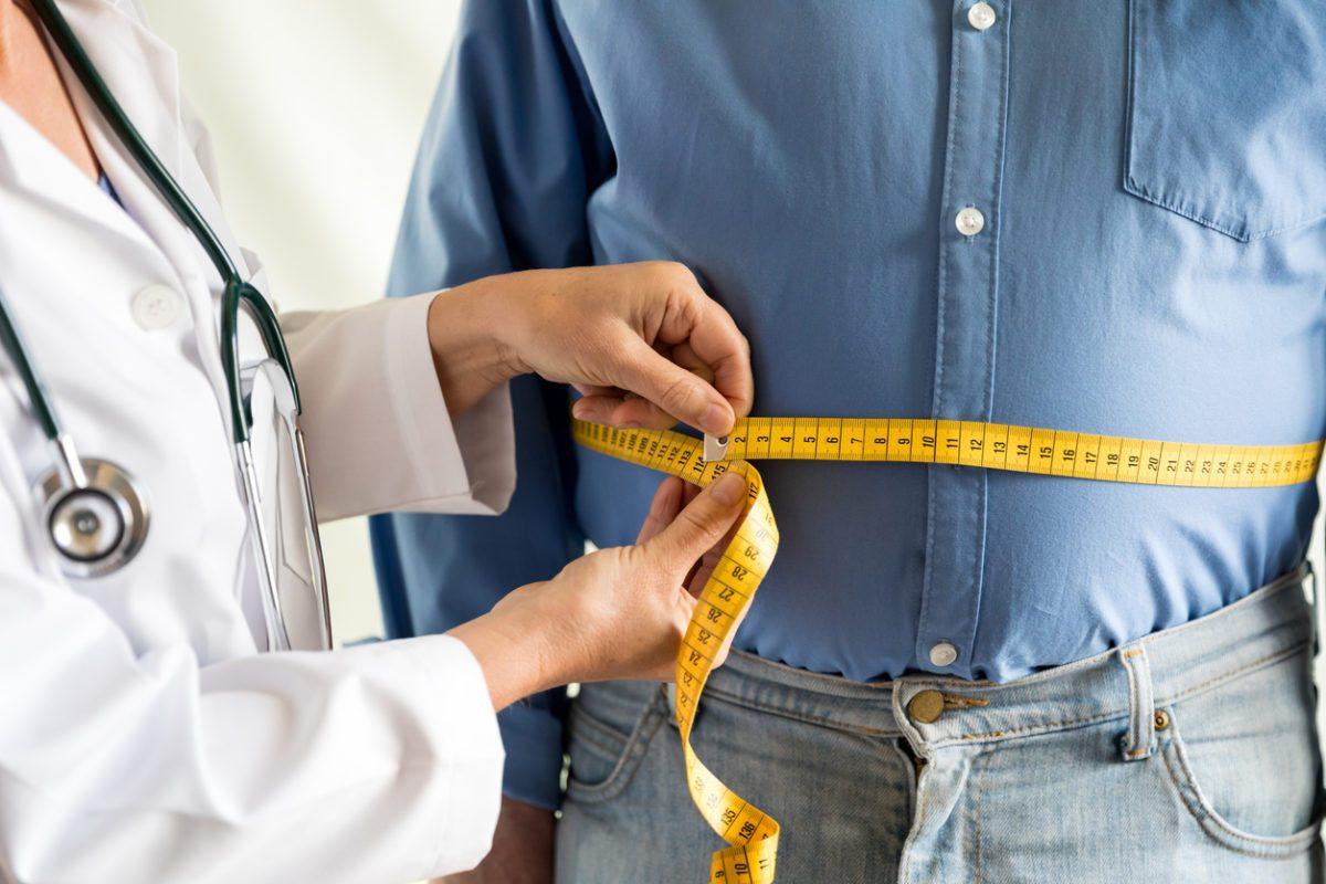 Мъж с напълняване в коремната област на преглед при лекар.