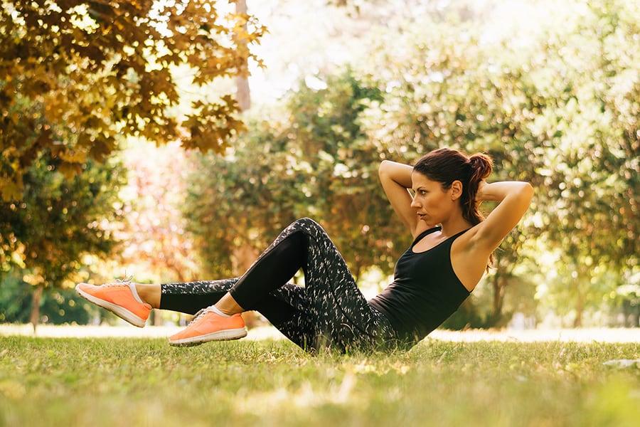 Жена прави физически упражнения в парка.