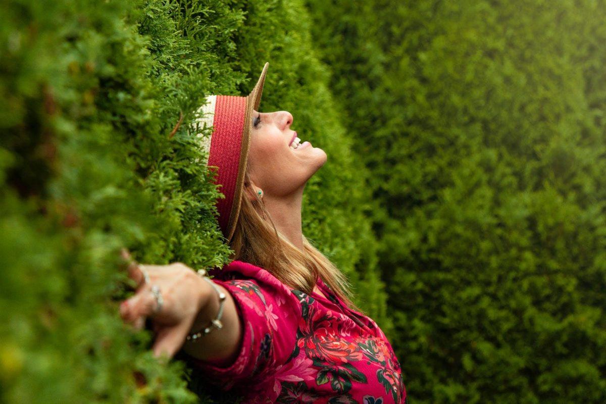 подсилване на имунитета - щастлива жена се обляга на храсти