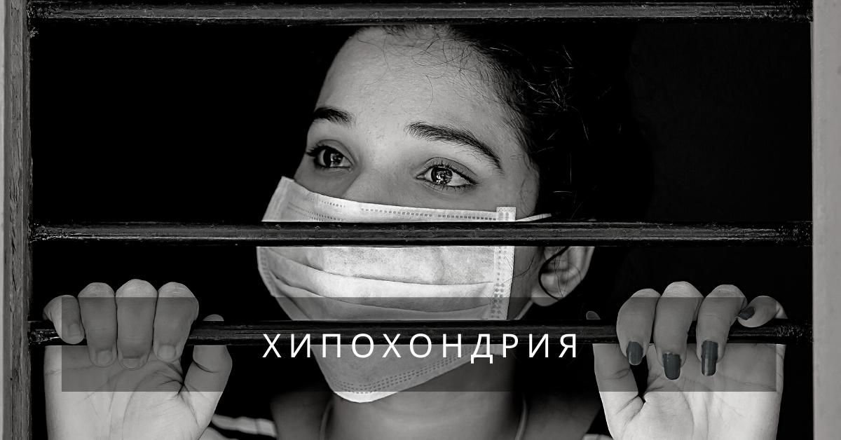 Жена с маска, която стои на прозорец с решетки.