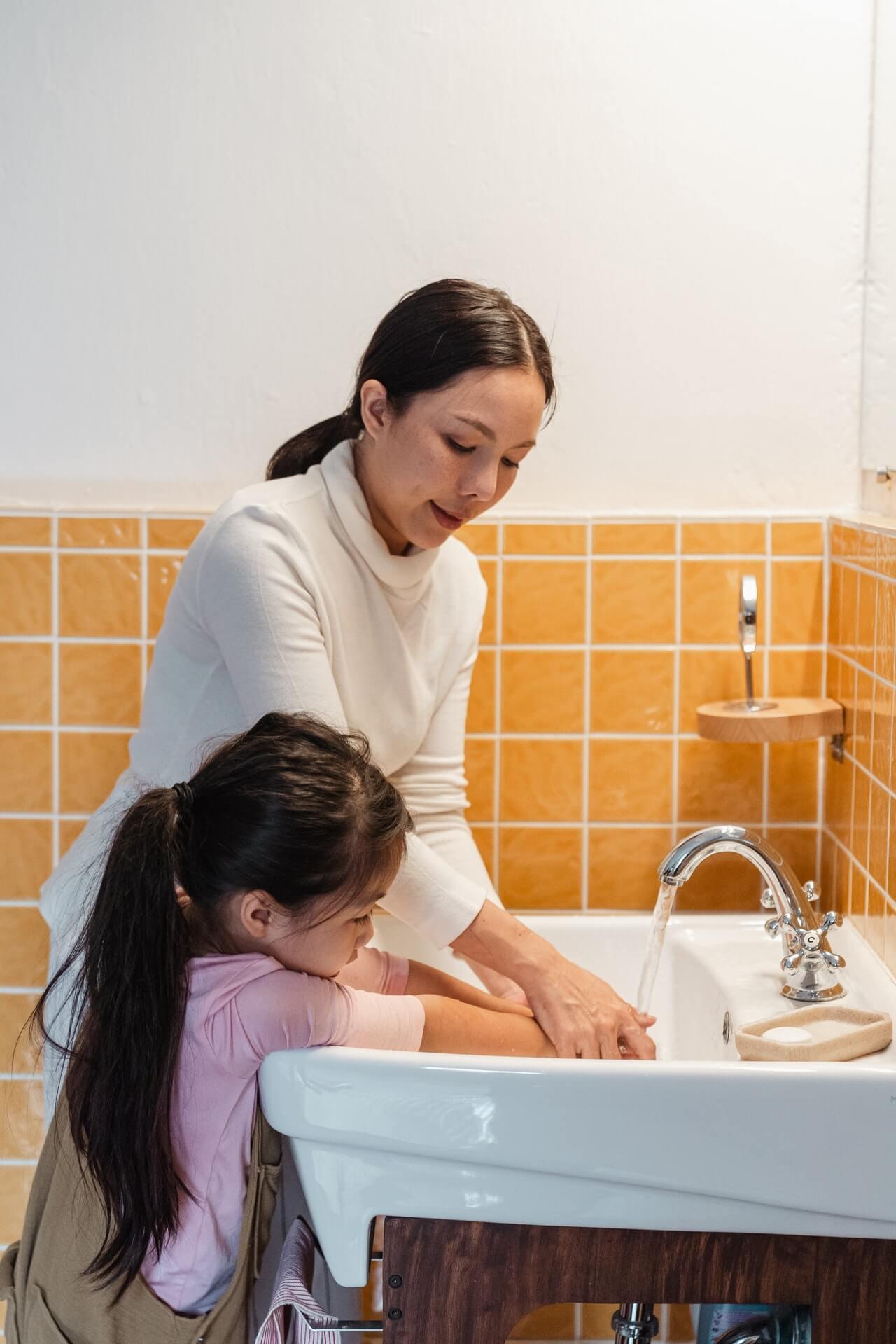 майка и дете си мият ръцете